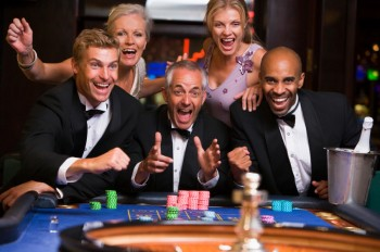 Five people in casino playing roulette smiling